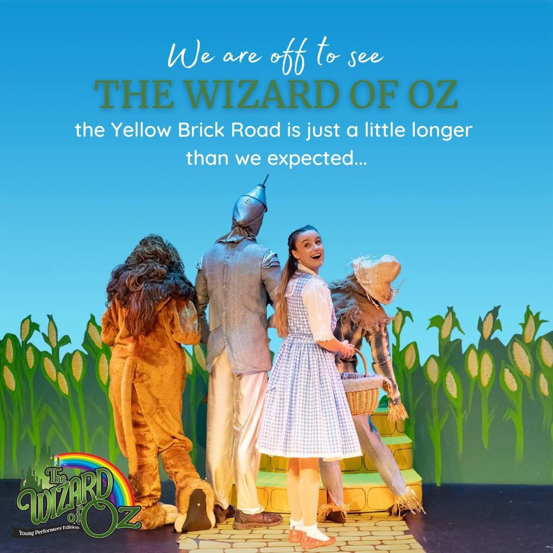 The backs of Dorothy, Lion, Tinman and Scarecow walking on the yellow brick road . Dorothy looking back over her shoulder.